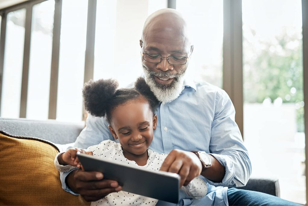 Grandfather and child using a tablet device